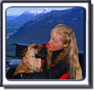 Blonde femal handler with Ebbey the Search Dog, a Rhodesian Ridgeback cross with a black muzzle, riding in a gondola.